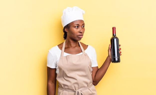 Czarna kobieta szefa kuchni afro czuje się smutna, zdenerwowana lub zła i patrzy w bok z negatywnym nastawieniem, marszcząc brwi w niezgodzie. koncepcja butelki wina