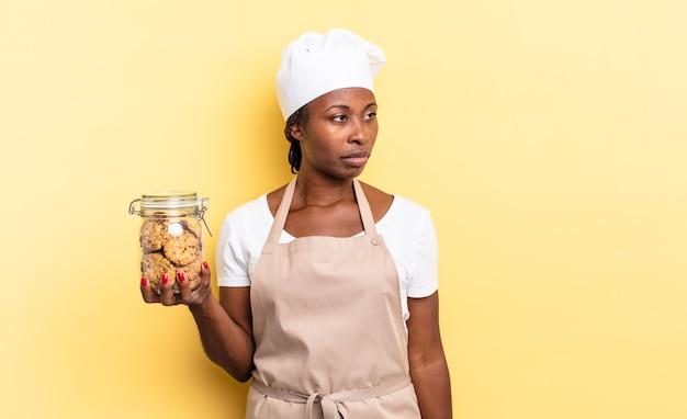 Czarna kobieta szefa kuchni afro czuje się smutna, zdenerwowana lub zła i patrzy w bok z negatywnym nastawieniem, marszcząc brwi w niezgodzie. koncepcja ciasteczek