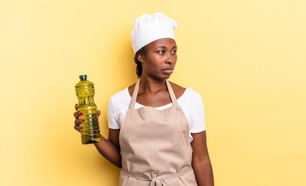 Czarna kobieta szefa kuchni afro czuje się smutna, zdenerwowana lub zła i patrzy w bok z negatywnym nastawieniem, marszcząc brwi w niezgodzie. koncepcja oliwy z oliwek