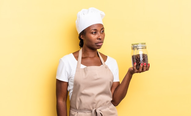 Czarna kobieta szefa kuchni afro czuje się smutna, zdenerwowana lub zła i patrzy w bok z negatywnym nastawieniem, marszcząc brwi w niezgodzie. koncepcja ziaren kawy