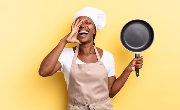 Czarna kobieta szefa kuchni afro czuje się szczęśliwa, podekscytowana i pozytywna, wydając wielki okrzyk z rękami przy ustach, wołając