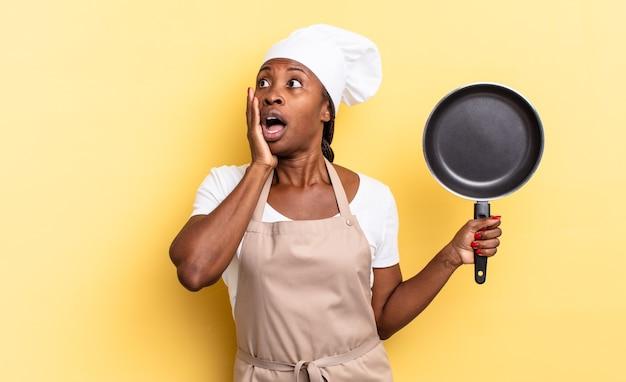 Czarna kobieta szefa kuchni afro czuje się szczęśliwa, podekscytowana i zaskoczona, patrząc w bok z obiema rękami na twarzy