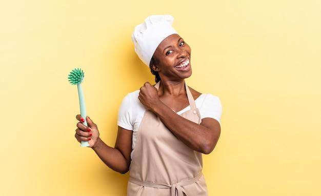 Czarna kobieta szefa kuchni afro czuje się szczęśliwa, pozytywna i odnosząca sukcesy, zmotywowana, gdy staje przed wyzwaniem lub świętuje dobre wyniki. koncepcja czyszczenia naczyń