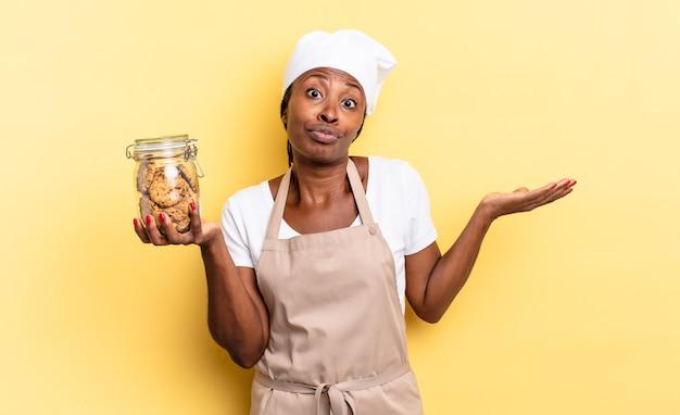 Czarna kobieta szefa kuchni afro czuje się zakłopotana i zdezorientowana, wątpi, waży lub wybiera różne opcje z zabawnym wyrazem twarzy. koncepcja ciasteczek