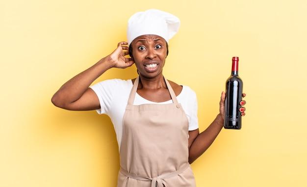 Czarna kobieta szefa kuchni afro czuje się zestresowana, zmartwiona, niespokojna lub przestraszona, z rękami na głowie, panikując z powodu błędu. koncepcja butelki wina