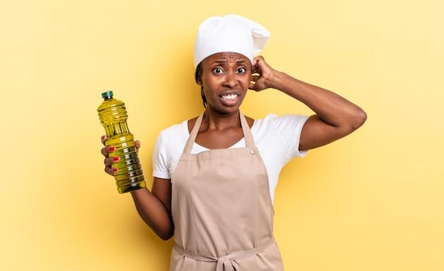 Czarna kobieta szefa kuchni afro czuje się zestresowana, zmartwiona, niespokojna lub przestraszona, z rękami na głowie, panikując z powodu błędu. koncepcja oliwy z oliwek