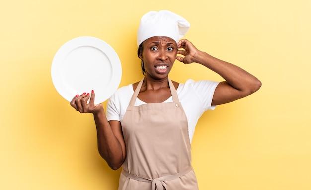 Czarna kobieta szefa kuchni afro czuje się zestresowana, zmartwiona, niespokojna lub przestraszona, z rękami na głowie, panikując z powodu błędu. koncepcja pustego talerza