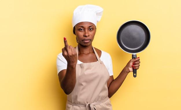 Czarna kobieta szefa kuchni afro czuje się zła, zirytowana, buntownicza i agresywna, machając środkowym palcem, walcząc