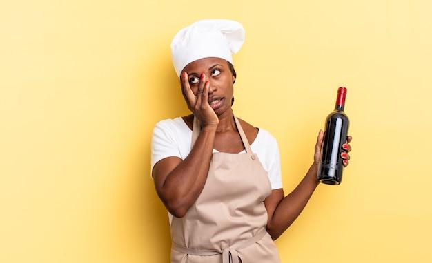 Czarna kobieta szefa kuchni afro czuje się znudzona, sfrustrowana i senna po męczącym, nudnym i żmudnym zadaniu, trzymając twarz ręką. koncepcja butelki wina