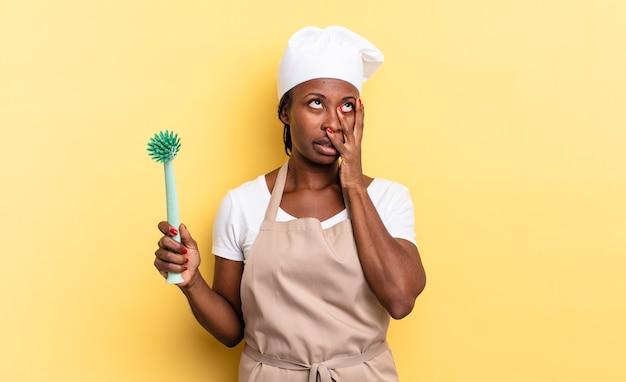 Czarna kobieta szefa kuchni afro czuje się znudzona, sfrustrowana i senna po męczącym, nudnym i żmudnym zadaniu, trzymając twarz ręką. koncepcja czyszczenia naczyń