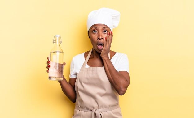 Czarna kobieta szefa kuchni afro czuje się zszokowana i przestraszona, wygląda na przerażoną z otwartymi ustami i rękami na policzkach trzymając butelkę wody