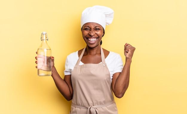 Czarna kobieta szefa kuchni afro czuje się zszokowana, podekscytowana i szczęśliwa, śmiejąc się i świętując sukces, mówiąc wow! trzyma butelkę wody