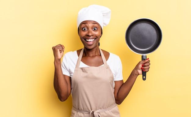 Czarna kobieta szefa kuchni afro czuje się zszokowana, podekscytowana i szczęśliwa, śmiejąc się i świętując sukces, mówiąc wow!