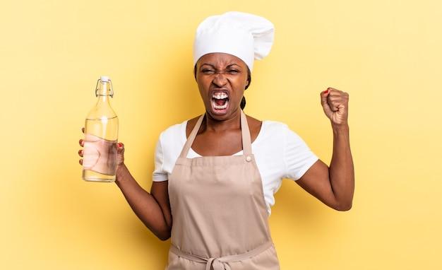 Czarna kobieta szefa kuchni afro krzyczy agresywnie z gniewnym wyrazem twarzy lub z zaciśniętymi pięściami świętuje sukces, trzymając butelkę wody