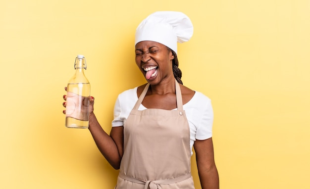 Czarna kobieta szefa kuchni afro o wesołej, beztroskiej, buntowniczej postawie, żartuje i wystawia język, bawi się trzymając butelkę wody
