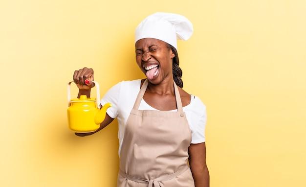 Czarna kobieta szefa kuchni afro o wesołej, beztroskiej, buntowniczej postawie, żartuje i wystawia język, dobrze się bawi. koncepcja czajnika