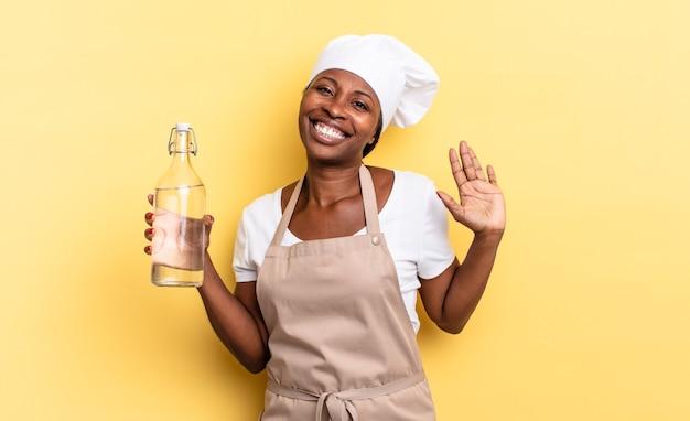 Czarna kobieta szefa kuchni afro uśmiecha się radośnie i radośnie, machając ręką, witając cię i pozdrawiając lub żegnając się z butelką wody