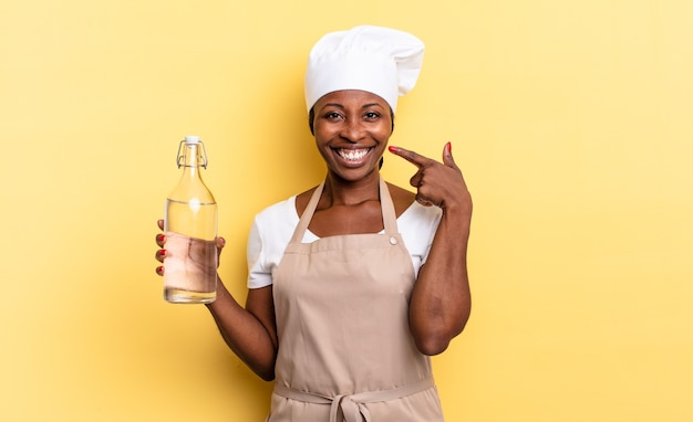 Czarna kobieta szefa kuchni afro uśmiechnięta pewnie, wskazując na swój szeroki uśmiech, pozytywna, zrelaksowana, zadowolona postawa trzymająca butelkę wody