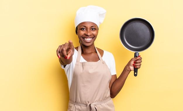 Czarna kobieta szefa kuchni afro wskazująca na aparat z zadowolonym, pewnym siebie, przyjaznym uśmiechem, wybierająca ciebie