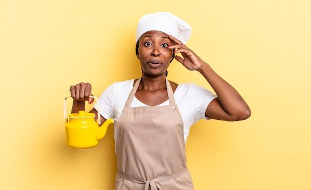 Czarna kobieta szefa kuchni afro wyglądająca na szczęśliwą, zdziwioną i zaskoczoną, uśmiechniętą i uświadamiającą sobie niesamowite i niewiarygodnie dobre wieści. koncepcja czajnika