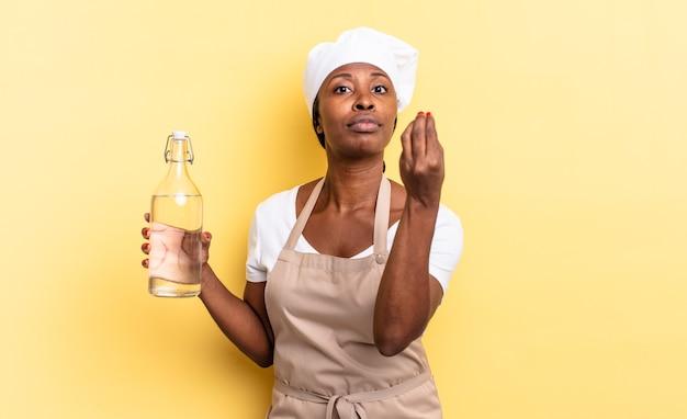 Czarna kobieta szefa kuchni afro wykonująca gest kaprysu lub pieniędzy, mówiąca o spłacie długów! trzyma butelkę wody