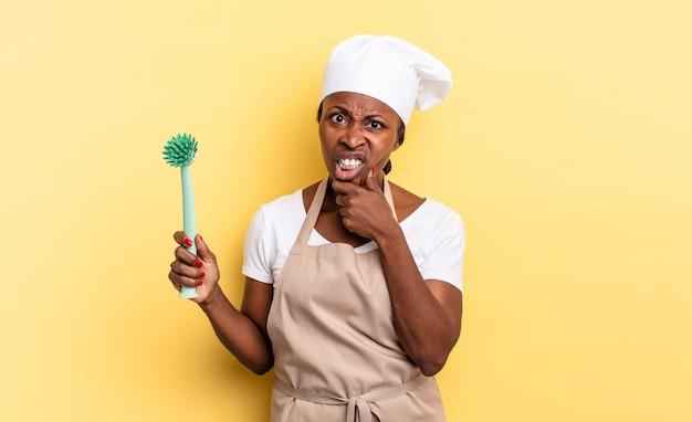 Czarna kobieta szefa kuchni afro z szeroko otwartymi ustami i oczami i ręką na brodzie, czując się nieprzyjemnie zszokowana, mówiąc co lub wow. koncepcja czyszczenia naczyń