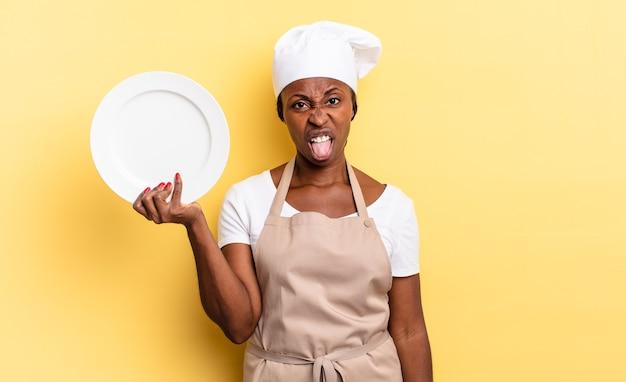 Czarna kobieta szefowa kuchni afro czuje się zdegustowana i zirytowana, wysuwa język, nie lubi czegoś paskudnego i obrzydliwego. koncepcja pustego talerza