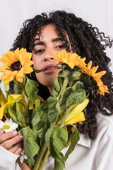 Czarna kobieta trzyma żółte kwiaty na twarzy