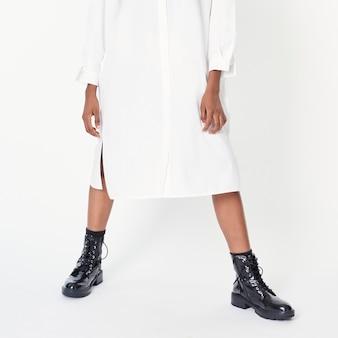 Czarna kobieta ubrana w botki z białą koszulową sukienkę