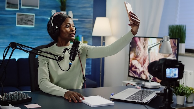 Czarna kobieta vlogerka robi selfie za pomocą smartfona podczas przesyłania treści na żywo w mediach społecznościowych