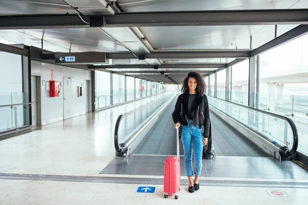 Czarna kobieta w ruchomym przejściu na lotnisku z różową walizką.