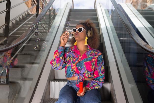 Czarna kobieta w zestawie słuchawkowym dmuchanie bąbelków siedzi na ruchomych schodach