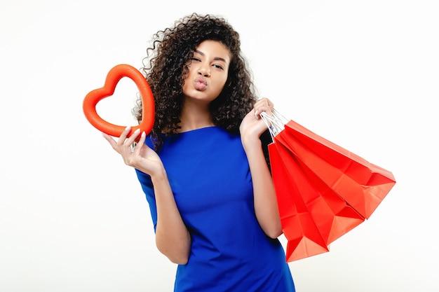 Czarna kobieta z czerwonym kierowym kształtem i torba na zakupy odizolowywającymi