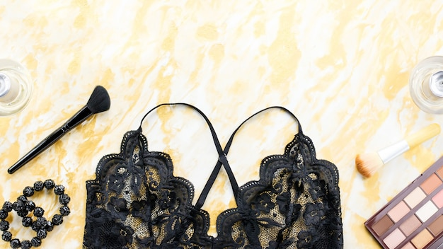 Czarna koronkowa bielizna z kosmetykami do makijażu, biżuterią w kolorze czarno-złotym