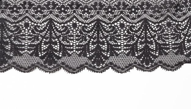 Czarna koronkowa tekstura z kwiatami na białym tle.
