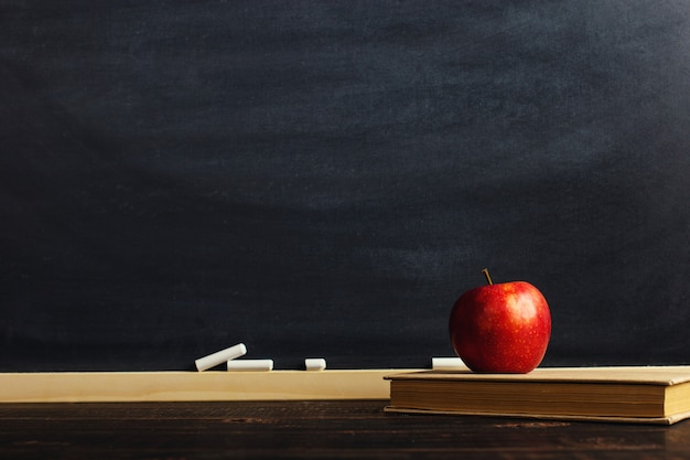 Czarna kredowa deska nad drewnianym stołem z książką i jabłkiem