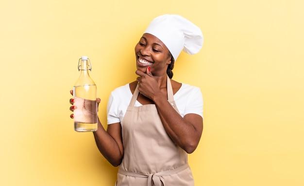 Czarna kucharka afro uśmiechnięta ze szczęśliwym, pewnym siebie wyrazem twarzy z ręką na brodzie, zastanawiająca się i patrząca w bok, trzymająca butelkę wody