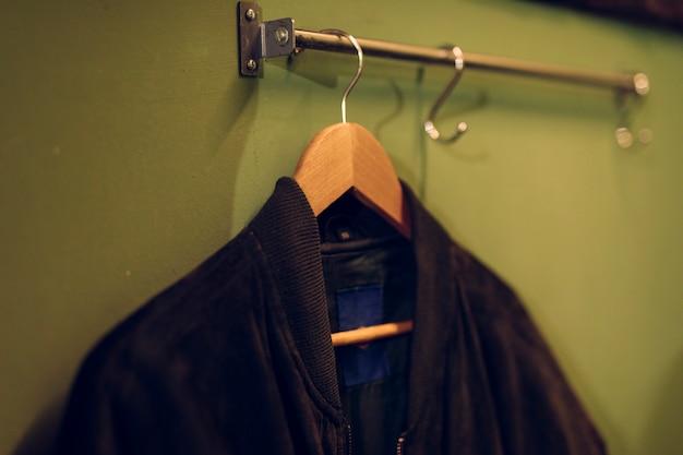 Czarna kurtka na drewnianym wieszaku zawieszona na szynie nad ścianą