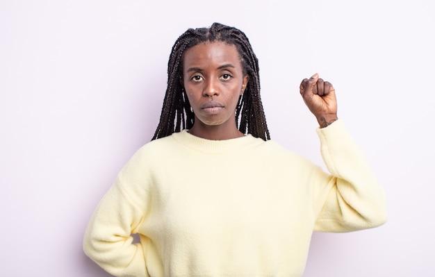 Czarna ładna kobieta czuje się poważna, silna i buntownicza, podnosi pięść, protestuje lub walczy o rewolucję