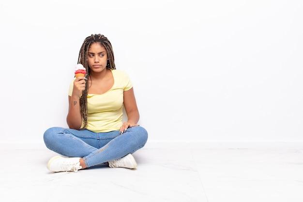 Czarna ładna kobieta siedzi na podłodze