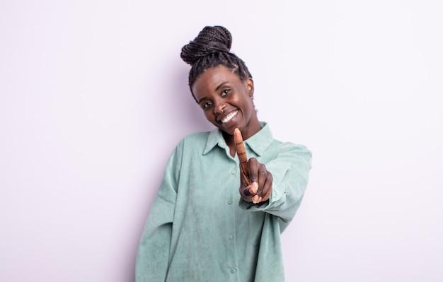 Czarna ładna kobieta uśmiechnięta i wyglądająca przyjaźnie, pokazująca numer jeden lub pierwsza z ręką do przodu, odliczająca w dół