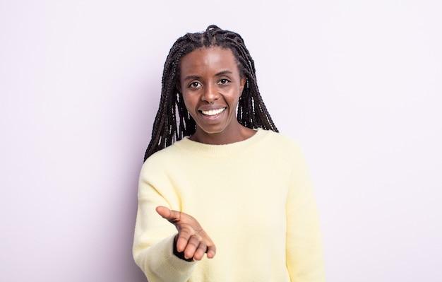 Czarna ładna kobieta uśmiechnięta, wyglądająca na szczęśliwą, pewną siebie i przyjazną, oferująca uścisk dłoni w celu zawarcia umowy, współpracująca