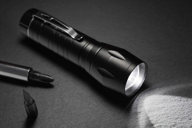 Czarna latarka na kamiennej powierzchni. narzędzia do pracy, poszukiwania i turystyki ..