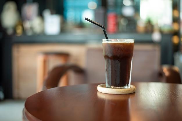 Czarna lodowa kawa na drewnianym biurku