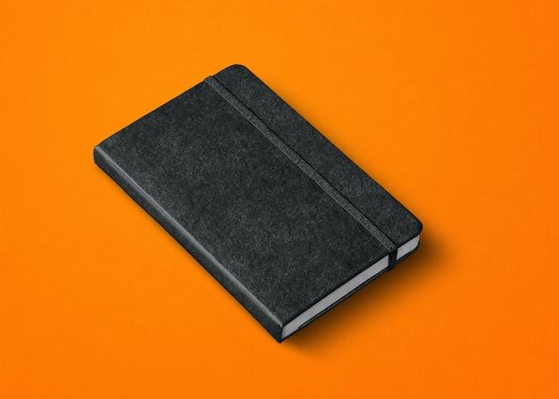 Czarna makieta zamkniętego notatnika na pomarańczowym tle