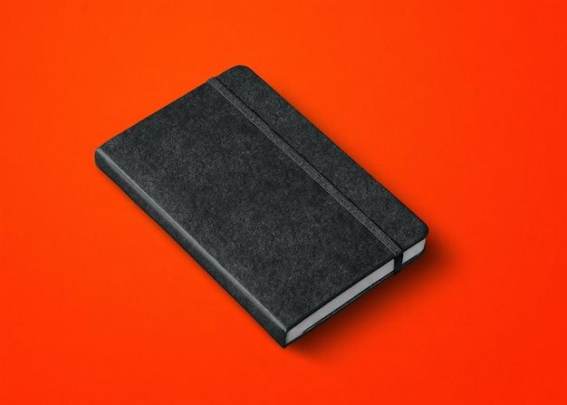 Czarna makieta zamkniętego notebooka na czerwonym tle