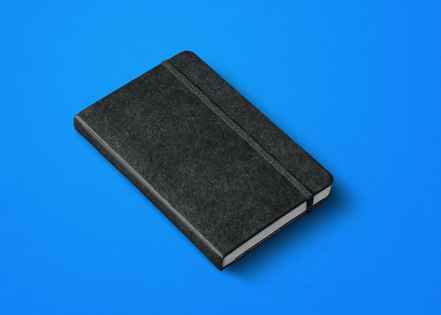 Czarna makieta zamkniętego notebooka na niebieskim tle