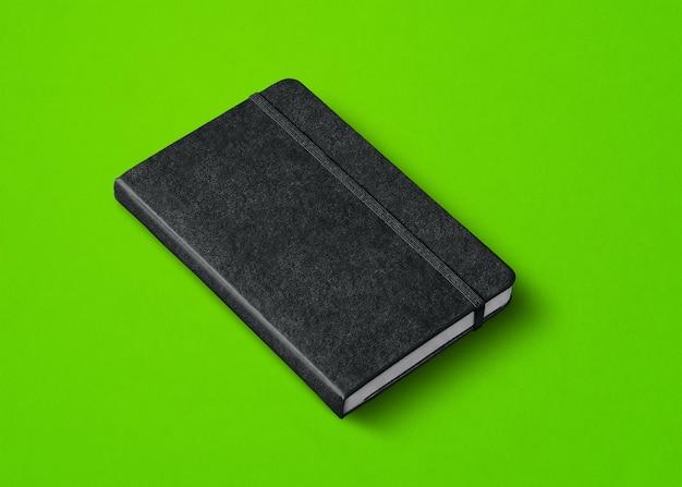 Czarna makieta zamkniętego notebooka na zielono
