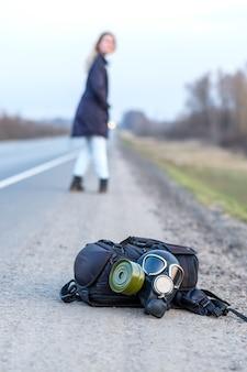 Czarna maska gazowa i plecak leżą na poboczu asfaltowej autostrady