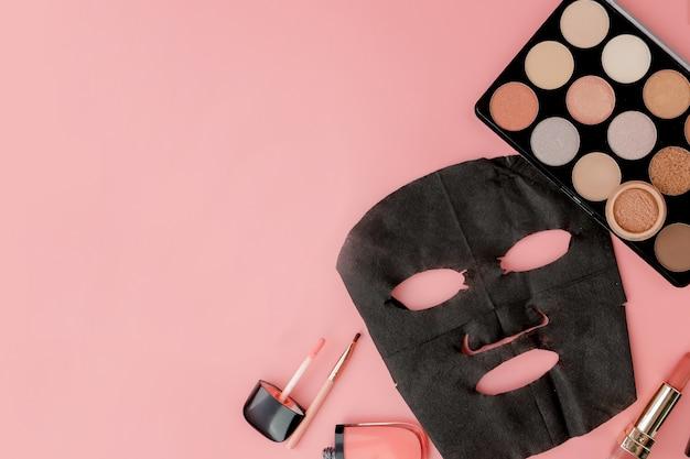Czarna maska kosmetyczna i makijaż na różowym tle z miejsca kopiowania